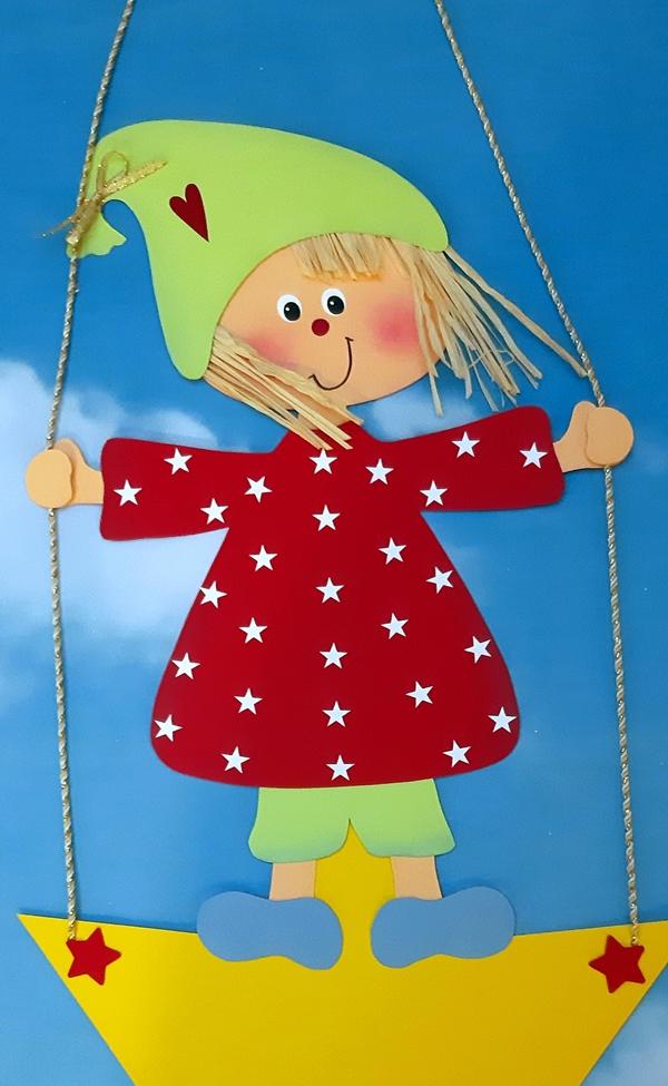 Fensterbild mit einem Weihnachtswichtel, der auf einem Stern schaukelt in rot und gelb.