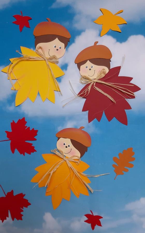3 fertig gebastelte Blätterkinder mit einem Hintergrund vom Himmel.