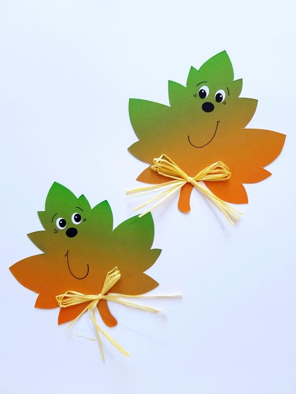 Bunte Blätter aus Bastelpapier mit einem lachenden Gesicht