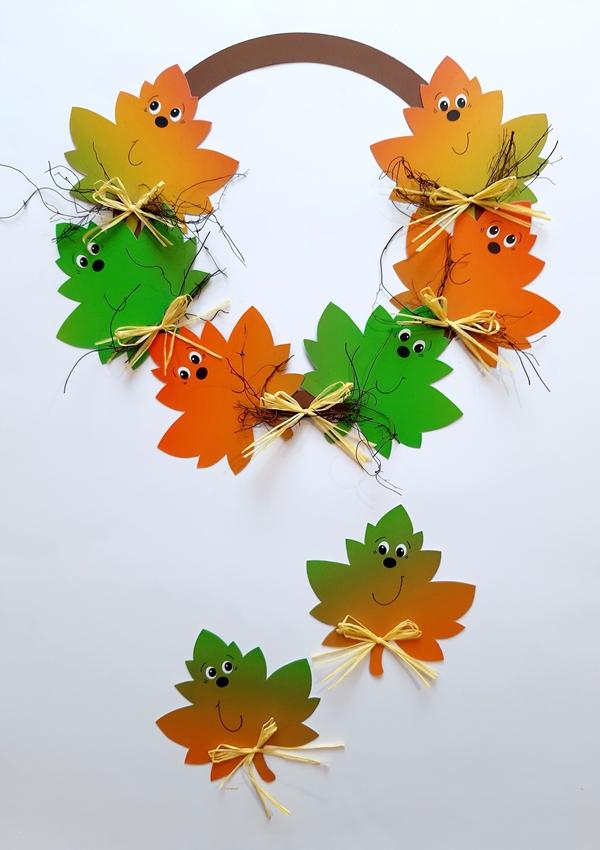 Bunte Blätter im Kranz aus Bastelpapier mit lachenden Gesichtern