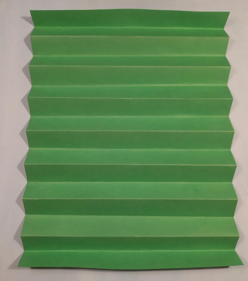 Die Faltungen vom Plissee auf grünem Papier.