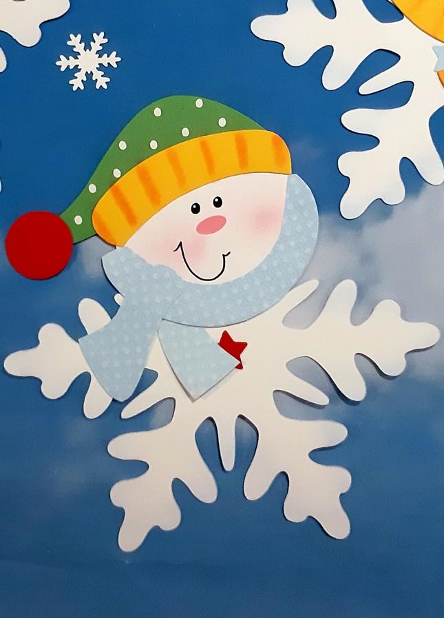 Schneeflocke aus papier mit Mütze und Schal.
