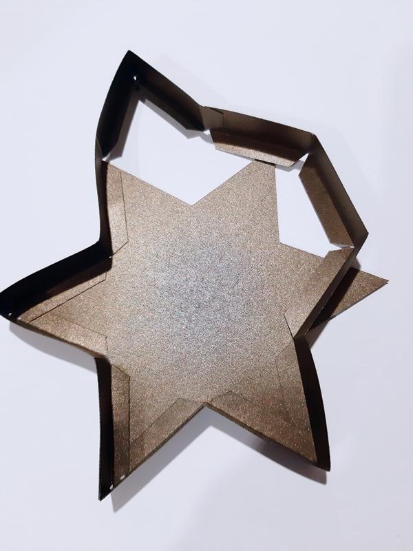 Ein Deckel von einer Sternschachtel wird zusammengeklebt.