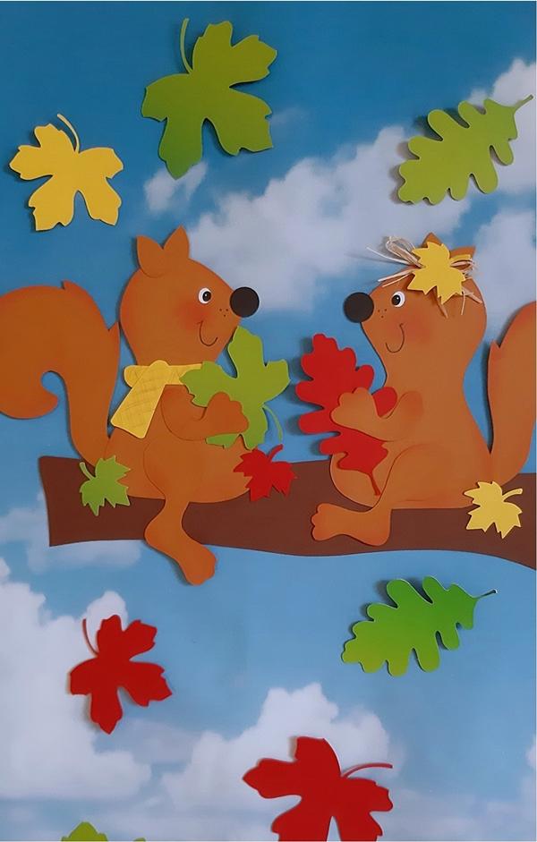 Zwei Eichhörnchen aus Papier auf einem Ast.
