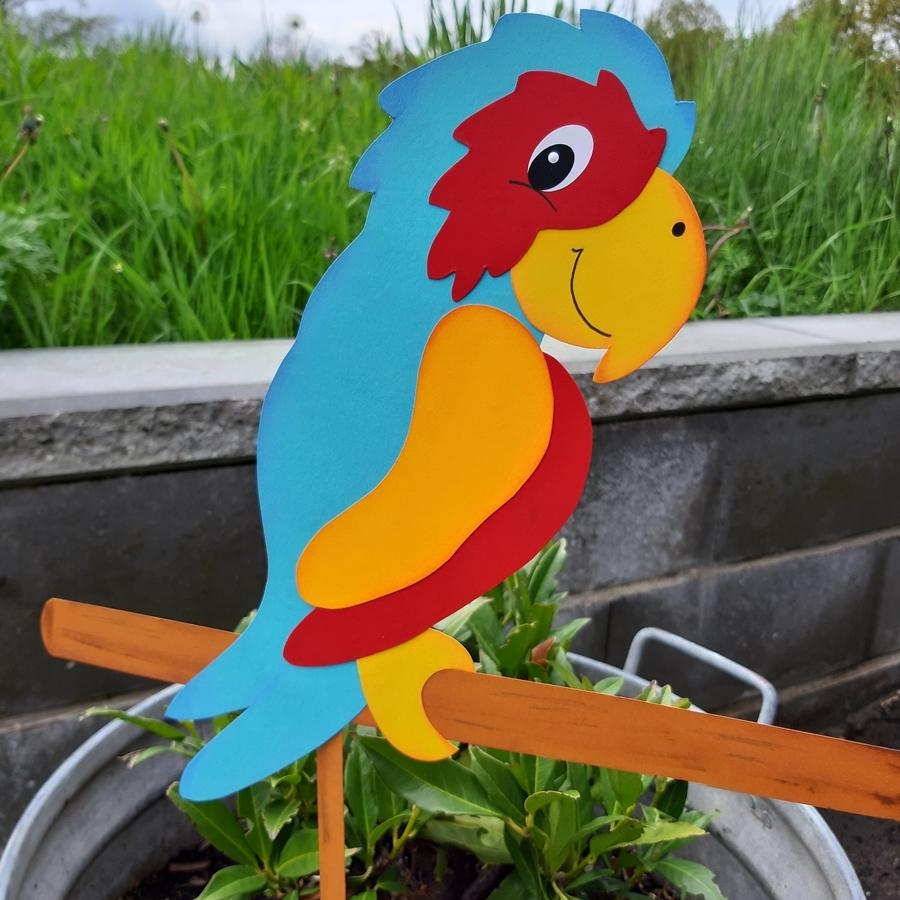 Ein Papagei aus Papier auf einer Sitzstange