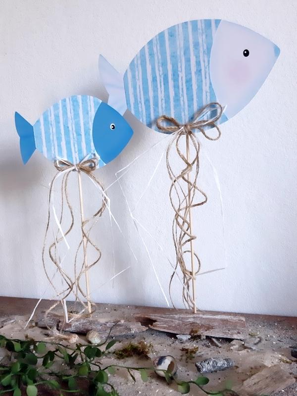 2 Fische aus Papier in blau und weiß am Holzstab