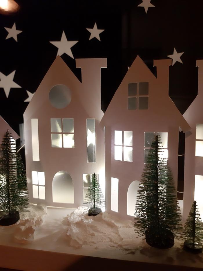 2 beleuchtete weiße Häuser.