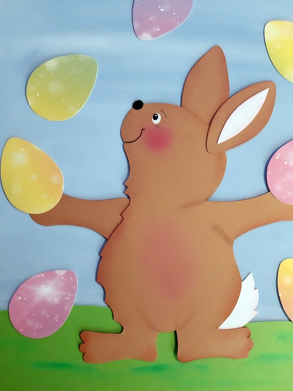 Fensterbild Osterhase beim Jonglieren mit bemalten Eiern
