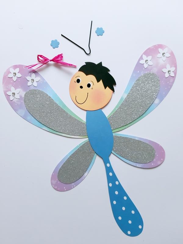 Fühler und eine Schleife werden an eine Libelle geklebt