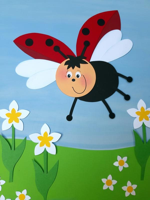 Fliegender Marienkäfer aus Papier fliegt hoch über eine Blumenwiese