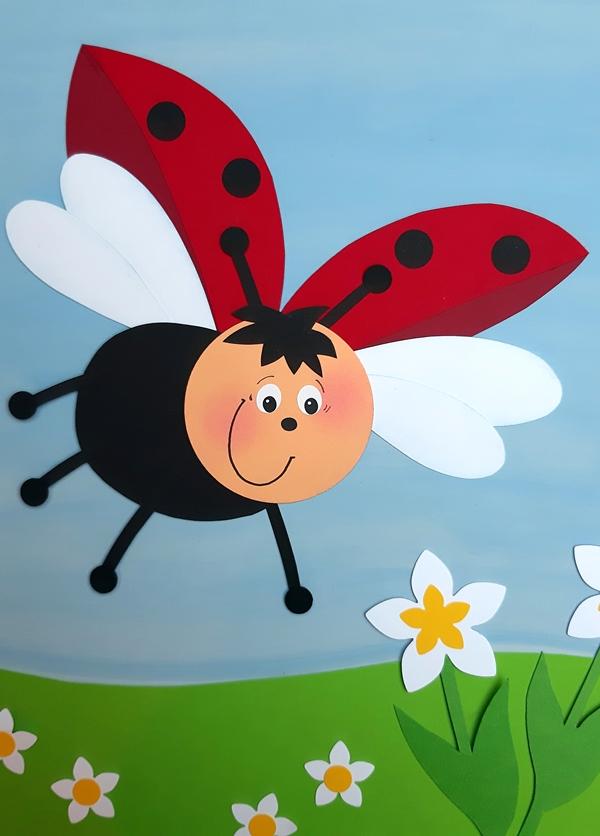 Fliegender Marienkäfer aus Papier fliegt über eine Blumenwiese