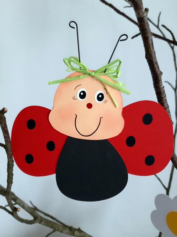 Eine Marienkäfer aus Fotokarton hängt am Zweig