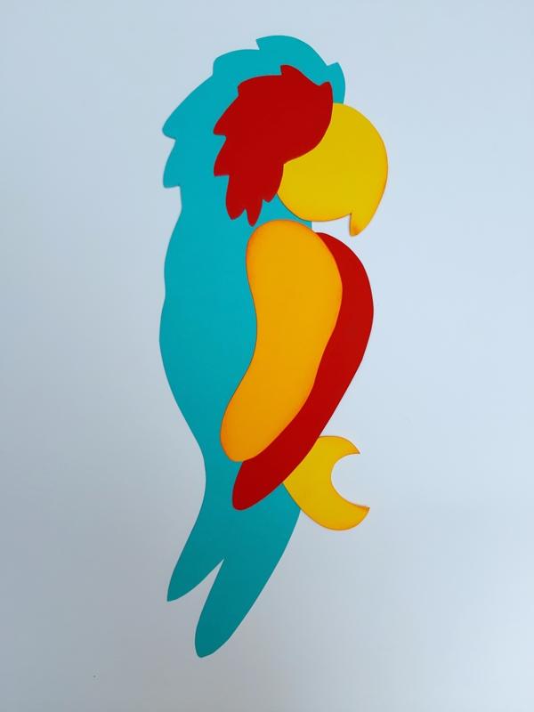 Ein Papagei aus Papier wird zusammengeklebt