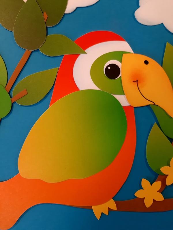 Ein bunter Paradies-Vogel aus Regenbogen-Fotokarton in der Detailansicht.