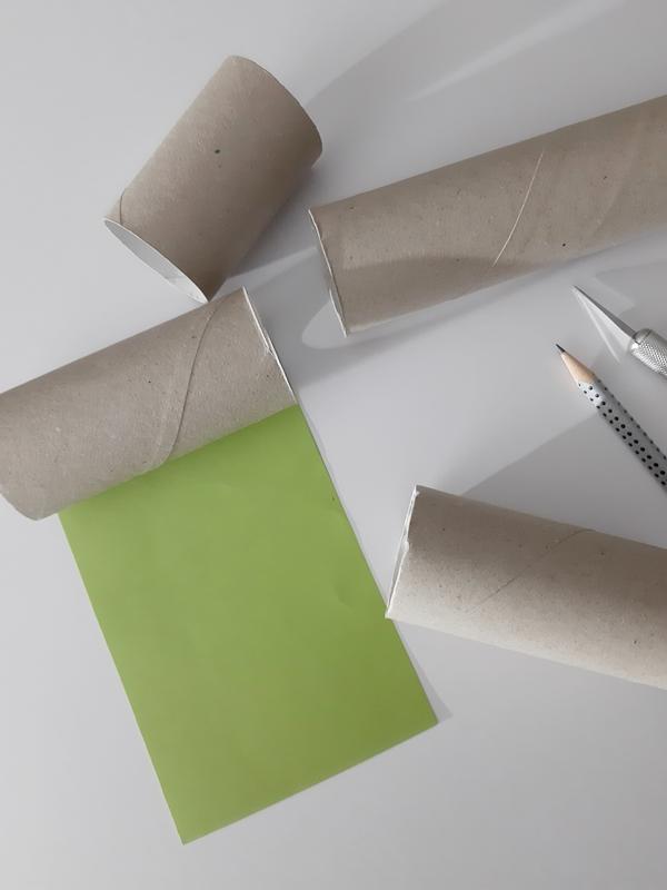 Eine Papprolle wird mit Tonpapier verkleidet