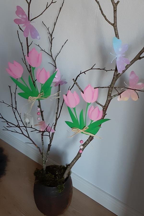 Eine Vase mit Zweigen und einer Frühlingsdeko aus Tulpen und Schmetterlingen