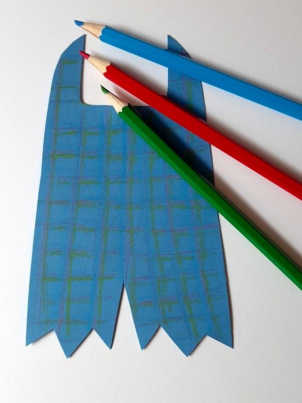 Ein Karomuster wird auf eine Hose aus Papier aufgemalt.