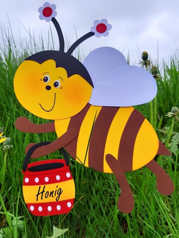 Biene mit Honigtopf auf einer Wiese