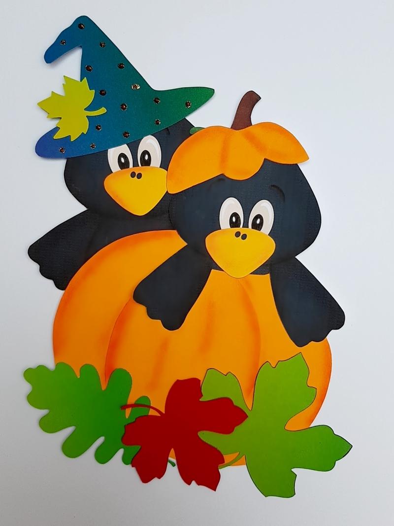 2 Halloween Krähen auf einem Kürbis.